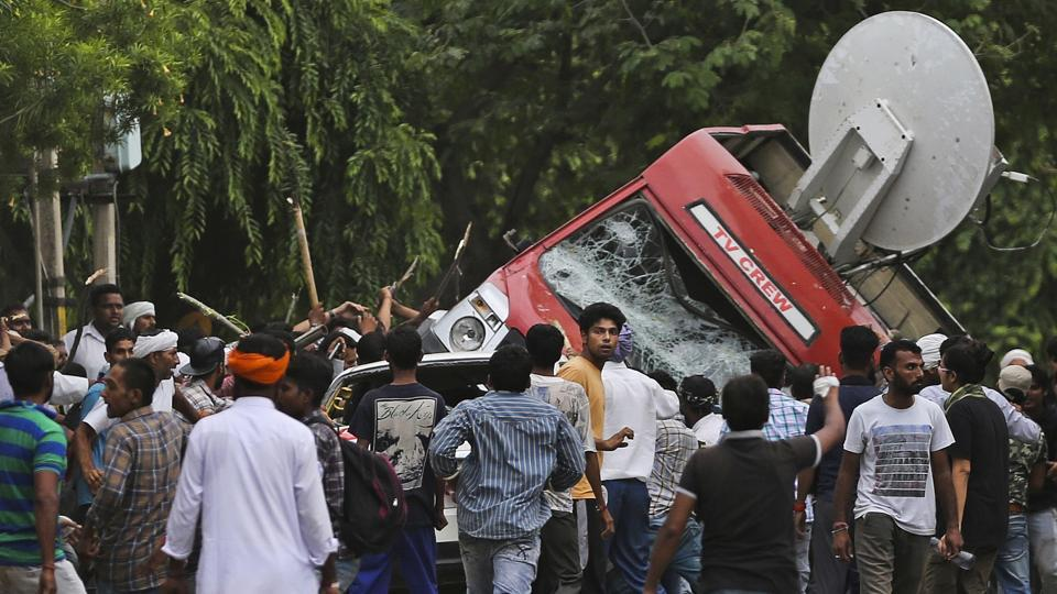 Dera Sacha Sauda sect members overturn an OB van on the streets of Panchkula on Friday. Deadly riots broke out in the town after a court convicted their guru, Gurmeet Ram Rahim Singh, of raping two of his followers. Mobs also attacked journalists and set fire to government buildings and railway stations.
