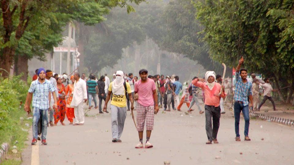 Supporters of Dera Sacha Sauda chief Gurmeet Ram Rahim pelt stones at security personnel, in Panchkula.