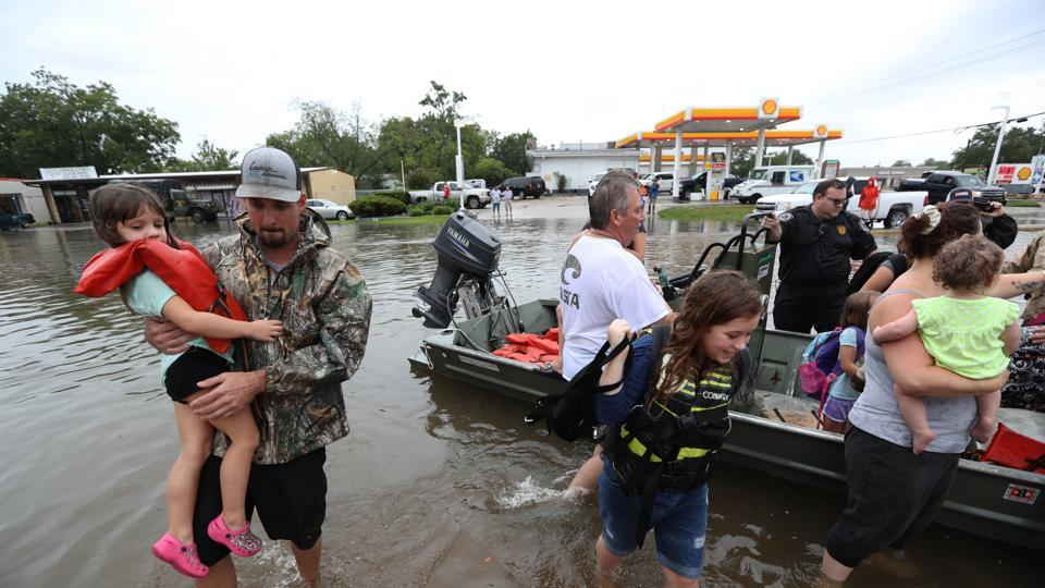Residents use their personal boats to rescue those stranded by floods on Sunday.