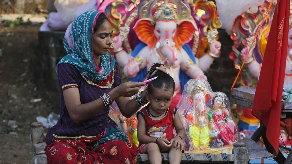 An Indian woman combs the hair of a child as she waits for customers for idols of the elephant headed Hindu god Ganesha ahead of Ganesh Chaturthi festival in Ahmedabad. (Ajit Solanki/AP)