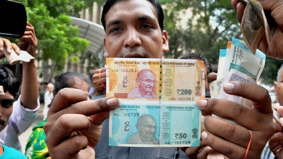 A man shows new currency notes of Rs 200 and Rs 50 outside the Reserve Bank of India in New Delhi on Friday. (PTI)