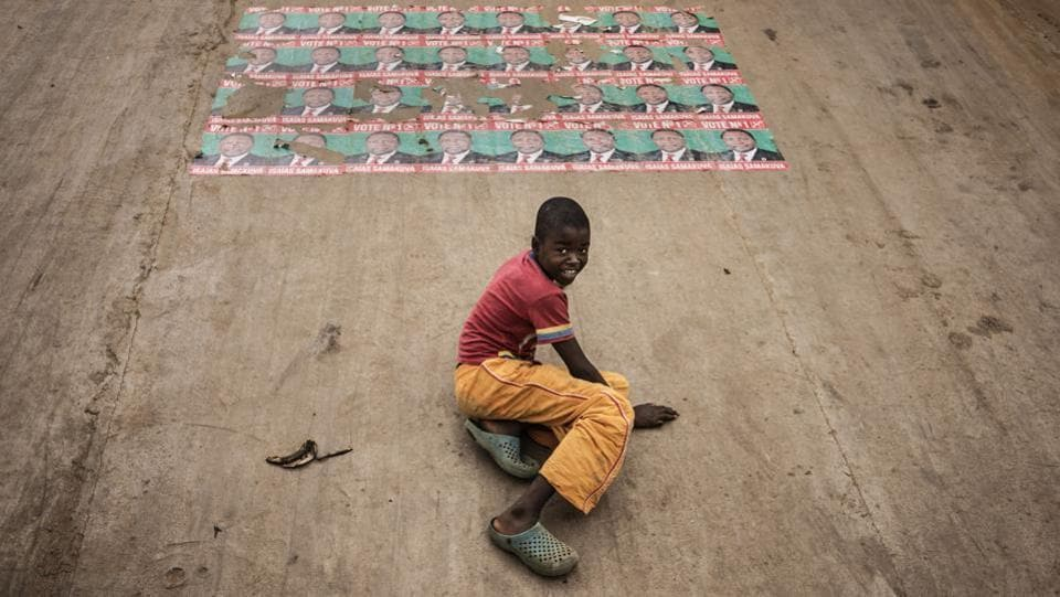 Electoral posters for Isaías Samakuva, the presidential candidate for the National Union for the Total Independence of Angola (UNITA) are sen plastered on the containment walls of a train track in the Viana district in Luanda, on August 22, 2017 as a boy slides down.  (Marco Longari/ AFP)