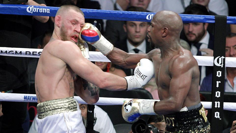 TBoxer Floyd Mayweather Jr. (R) lands a right to the face of mixed martial arts star Conor McGregor during their fight at the T-Mobile Arena in Las Vegas, Nevada on August 26, 2017. Floyd Mayweather outclassed Conor McGregor with a 10th-round stoppage on August 26 to win their money-spinning superfight and clinch his 50th straight victory.  (John Gurzinski/ AFP)