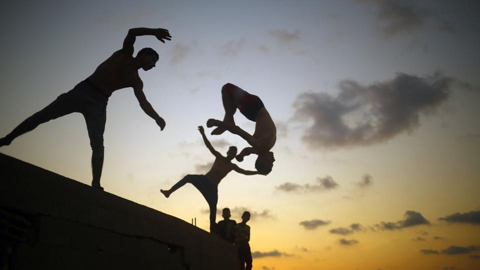 Palestinian youths practice parkour by the beach at dusk in Gaza City on August 25. (Mohammed Abed/ AFP)