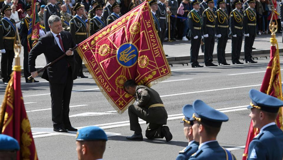 A unit commander pays honor to a flag hold by Ukrainian President Petro Poroshenko (L) during a military parade in Kiev on August 24, 2017 to celebrate the Independence Day. (Genya Savilov/ AFP)