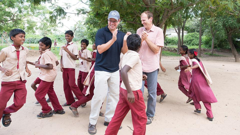 Matt Damon and Gary White with school children in India.