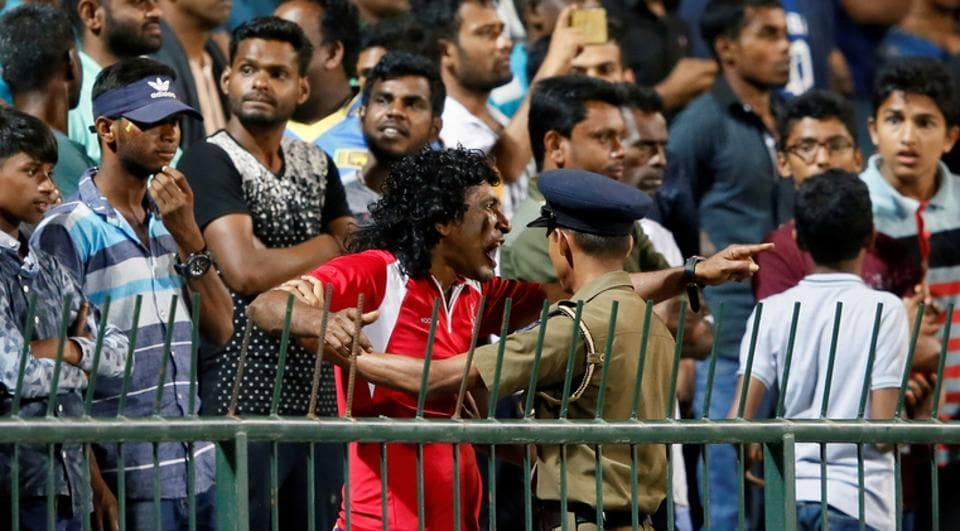 An angry Sri Lankan fan shouts at Sri Lankan players as a police officer tries to stop him during the third ODI against Sri Lanka.