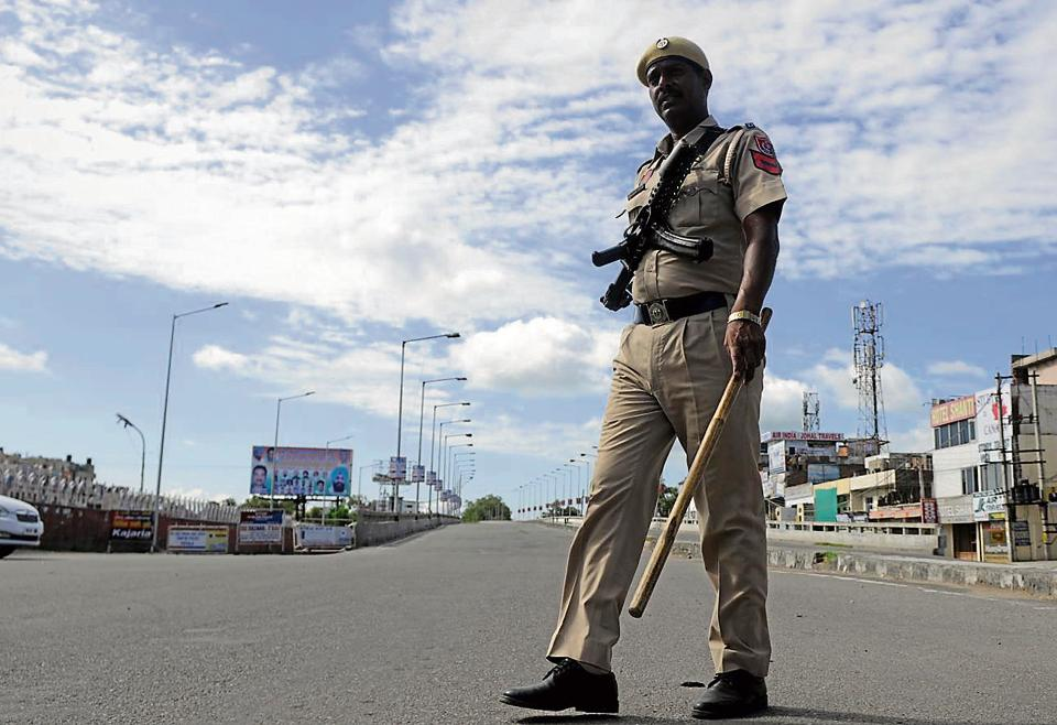 Apoliceman stands guard during curfew in Patiala on Monday.