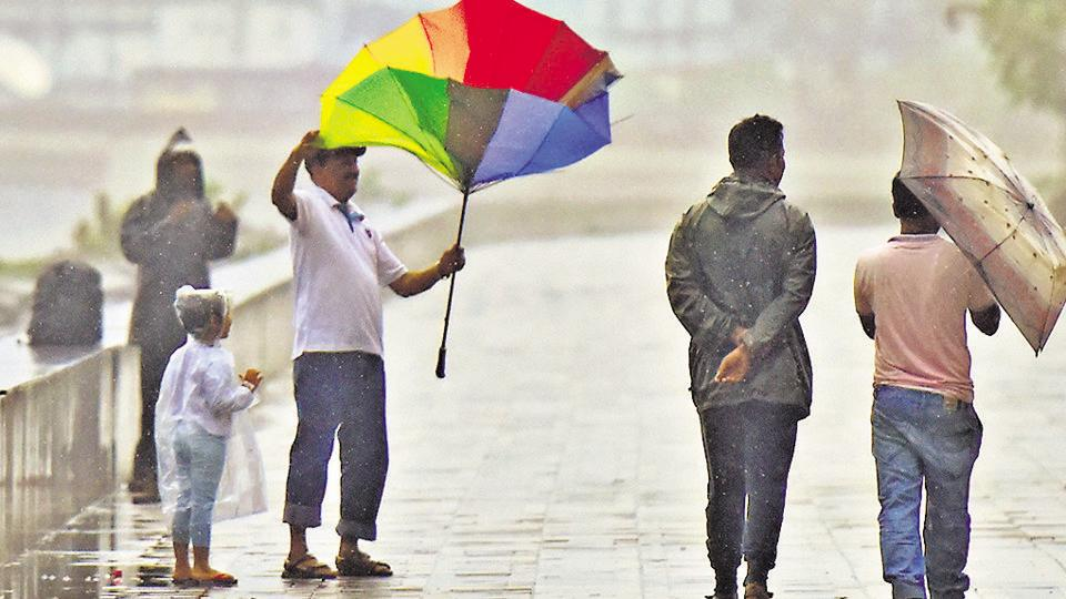 A man does a balancing act with his umbrella in Mumbai on Monday.