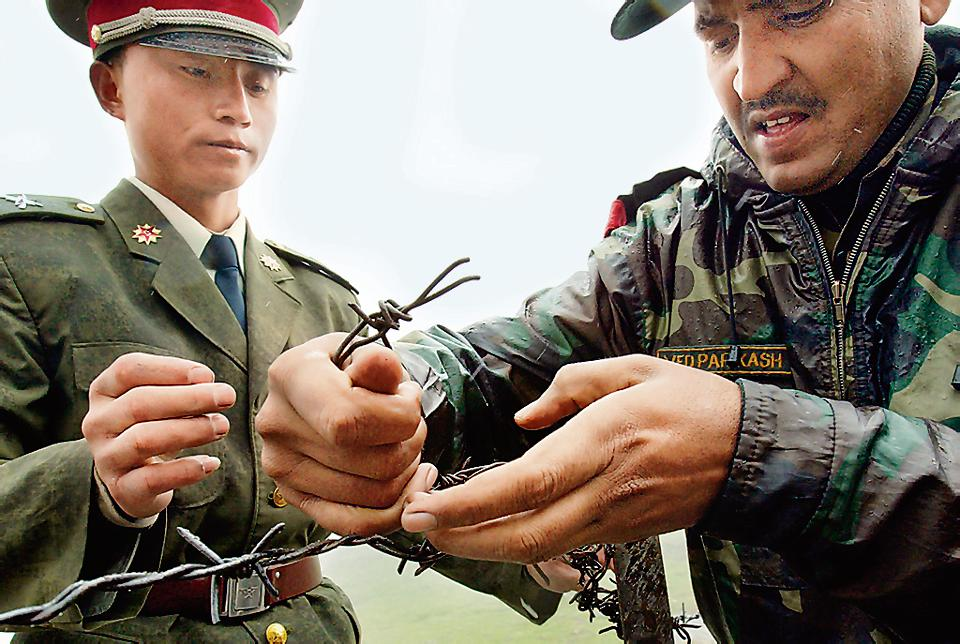 (FILES) A file photo of a Chinese soldier (L) and an Indian soldier placing a barbed wire fence following a meeting of military representatives at the Nathu La border in  Sikkim, India. India said  on August 28, 2017 that troops were disengaging from a months-long stand-off with the Chinese military on a strategically important area of disputed territory in the Himalayas.
