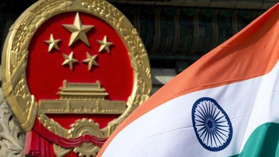 A file photo of an Indian flag flying next to the Chinese national emblem.
