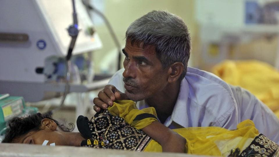 A relative attends to a child receiving treatment at the state-run Baba Raghav Das Medical College Hospital in Gorakhpur, Uttar Pradesh on August 13.