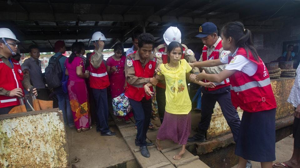 Members of Myanmar Red Cross help a disable woman who fled from unrest in Maungdaw as she arrives in Sittwe jetty, Tuesday, Aug. 29, 2017, in Sittwe, Rakhine State, western Myanmar.