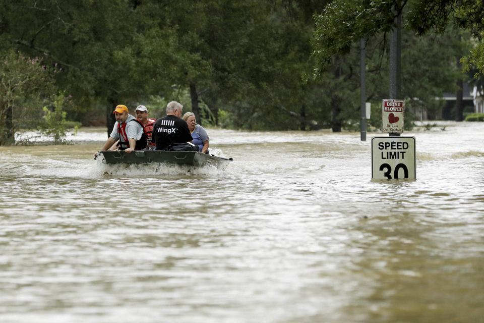 People are evacuated by boat as floodwaters from Tropical Storm Harvey rise,  in Kingwood, Texas, on Tuesday.