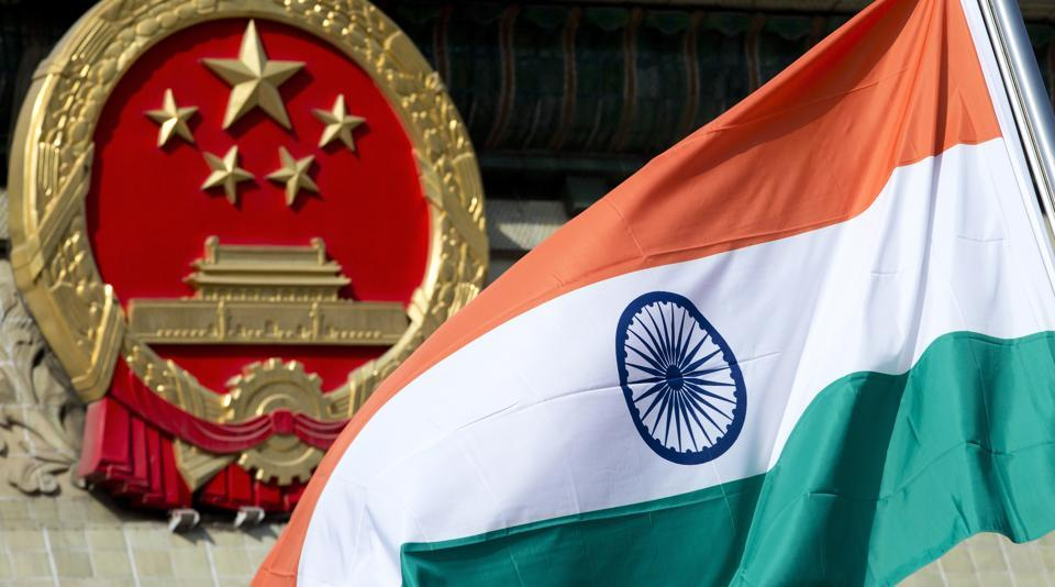 Indian national flag is flown next to the Chinese national emblem during a welcome ceremony for visiting Indian officials outside the Great Hall of the People in Beijing.