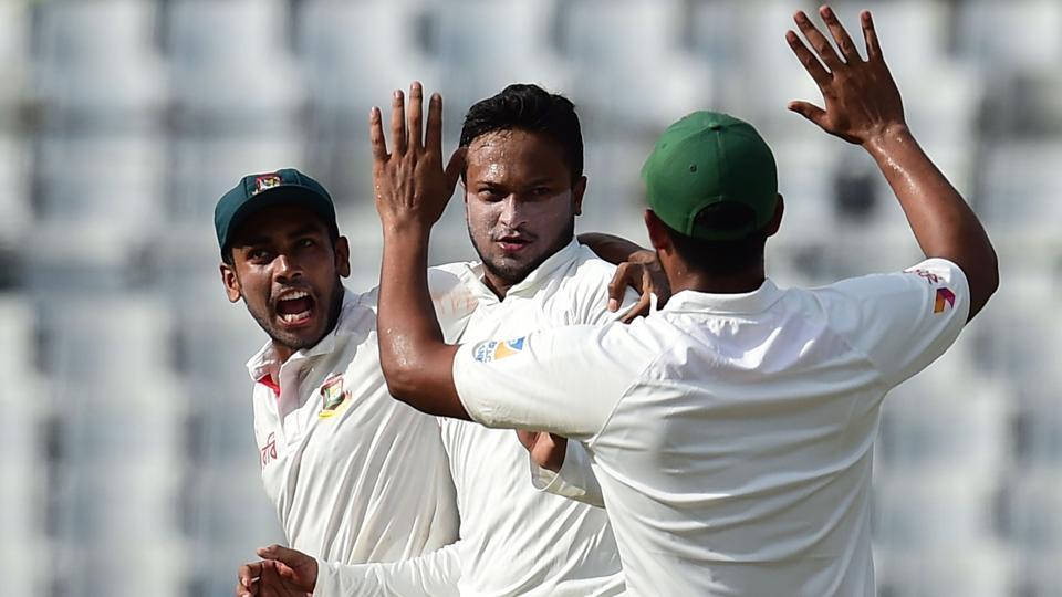 Bangladesh cricketer Shakib Al Hasan (C) celebrates with his teammate Mehedi Hasan (L) after the dismissal of Australian cricketer Usman Khawaja.