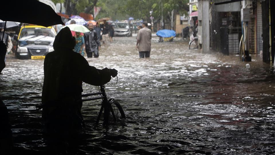 People move through a waterlogged street following heavy rains in Mumbai, India, Tuesday, Aug. 29, 2017. Heavy rains Tuesday brought Mumbai to a halt flooding vast areas of the city.