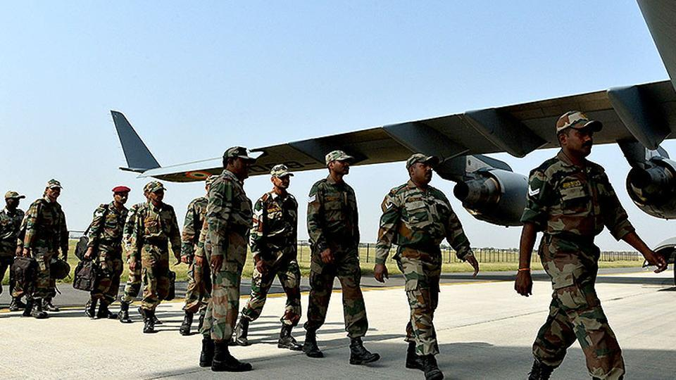Army personnel board an Indian Air Force aircraft at Hindon Air Force Station in Ghaziabad.
