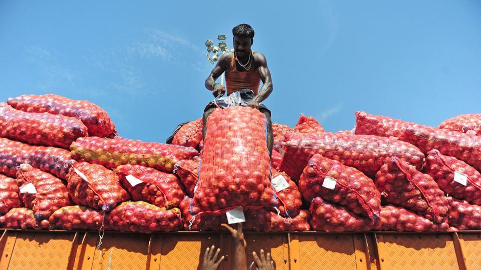 Indian labourers unload sacks of onion from a truck at a wholesale market in Chennai on June 1, 2016.