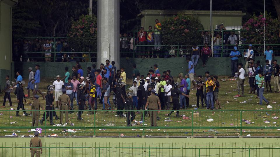Sri Lankan police personnel ask people to leave after some spectators threw plastic bottles in the ground to disrupt play during the third One-Day International (ODI)between Sri Lanka and India in Pallekele on Sunday.