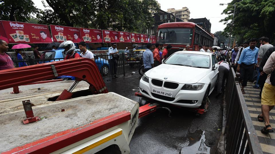 Mumbai Police tweeted: If your car is out of fuel/stranded #Diall100 or 8454999999 or tweet us for free towing till the nearest fuel pump or garage. The traffic police has been towing away vehicles left behind by commuters as water levels surged on Tuesday. (Vijayanand Gupta/HT Photo)