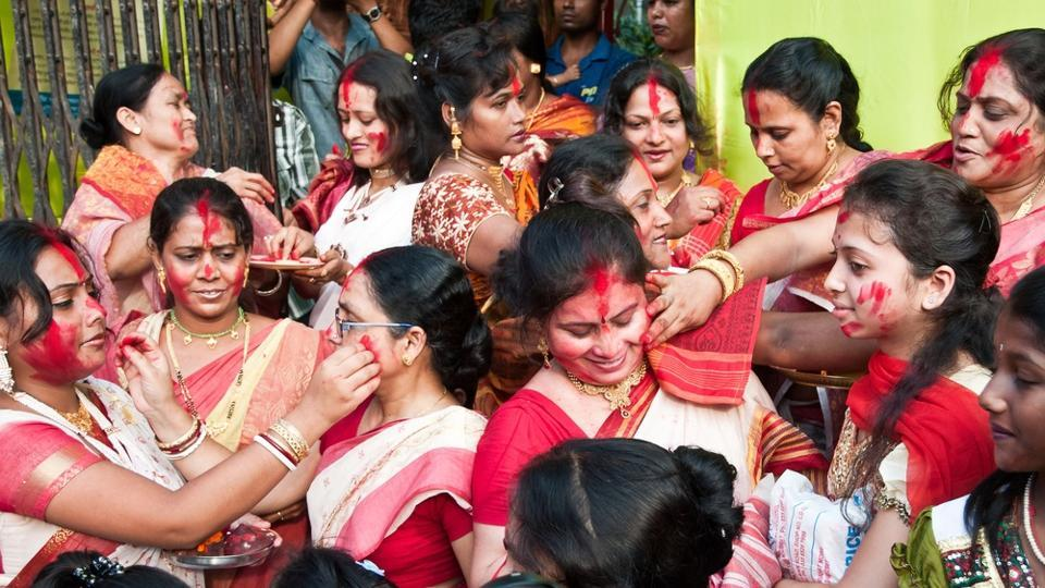 Married Bengali Hindu women smear and play with vermilion during Sindur Khela traditional ceremony on the final day of Durga Puja festival.