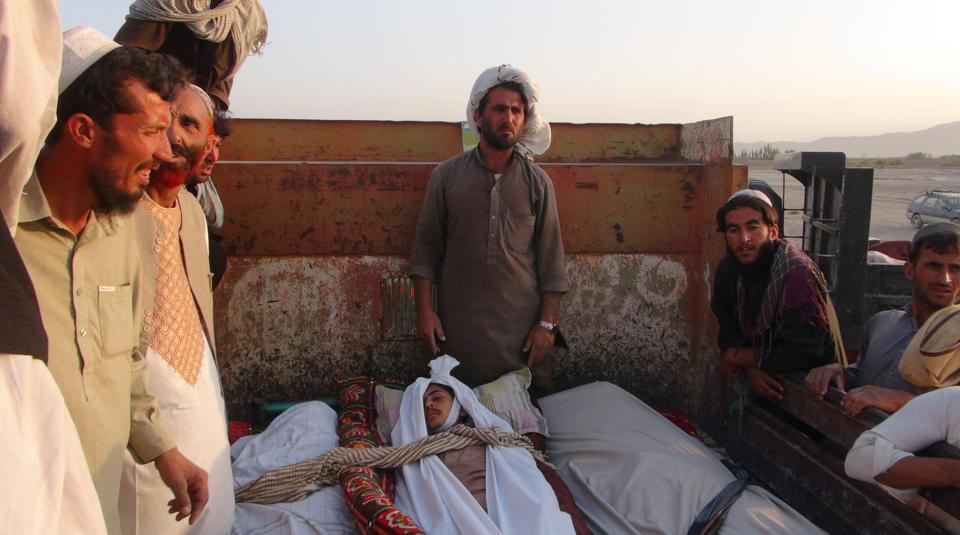 In this picture taken on August 30, 2017 Afghan men sit next to dead bodies of those allegedly killed in a US air strike in Dasht-e-Bari village in Logar province near Kabul.