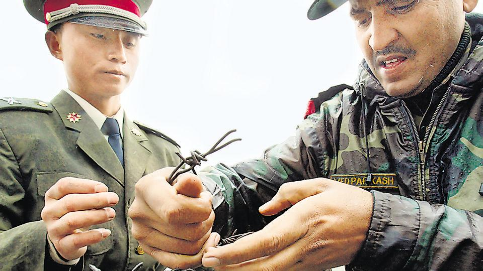 File photo from July 2006 shows a Chinese soldier (left) and an Indian soldier placing a barbed wire fence following a meeting of military representatives at Nathu La border crossing in India's northeastern Sikkim state.