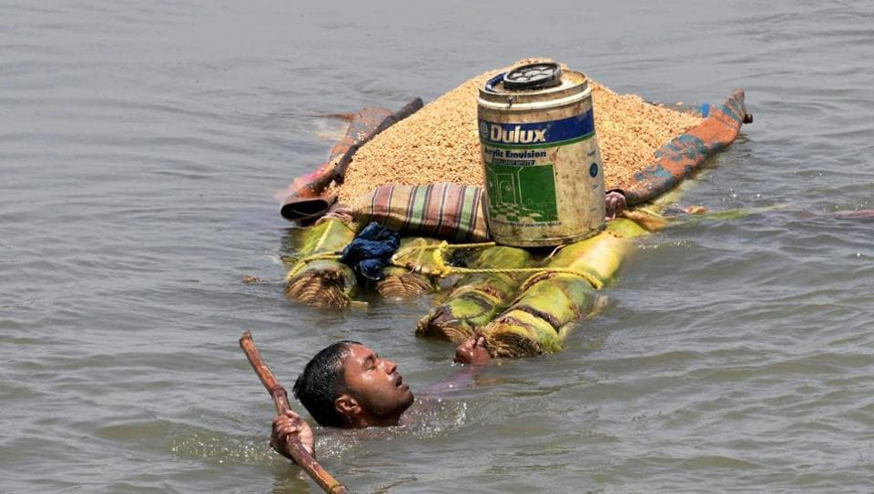 A villager carries his belongings on a makeshift raft from a flooded village in Araria district of Bihar .