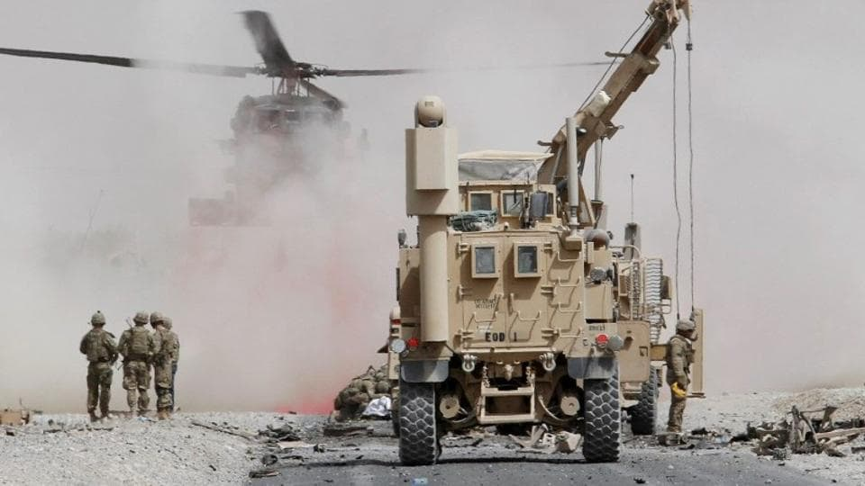 FILE PHOTO: U.S. troops assess the damage to an armoured vehicle of NATO-led military coalition after a suicide attack in Kandahar province, Afghanistan August 2, 2017.
