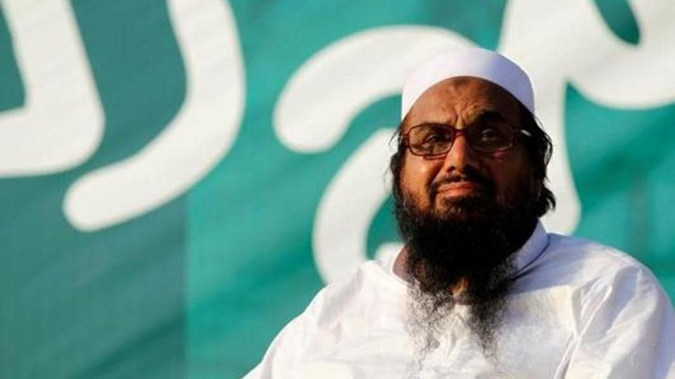 Hafiz Muhammad Saeed, chief of the banned Islamic charity Jamat-ud-Dawa, looks over the crowed as they end a