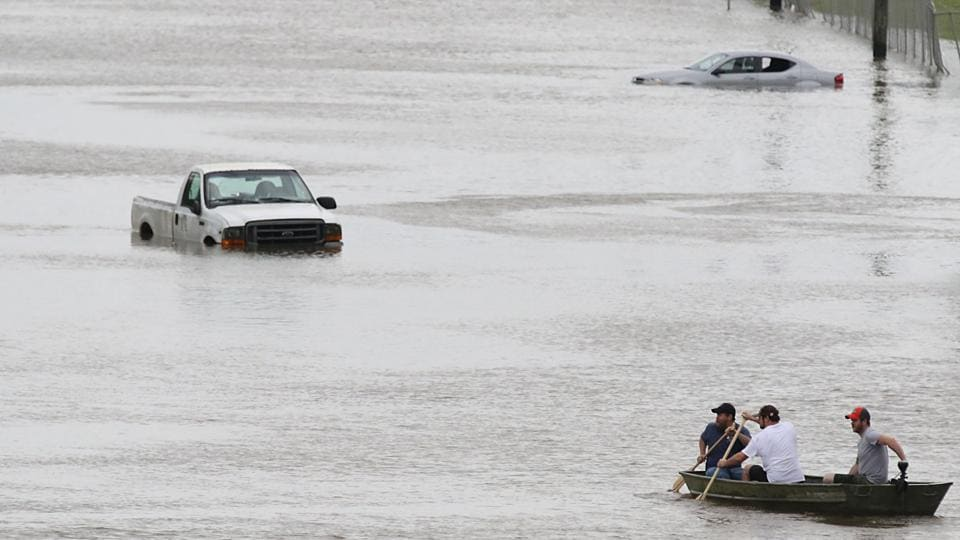 Men paddle a boat on the flooded waters of Telephone Rd. in Houston, Texas on August 30, 2017.