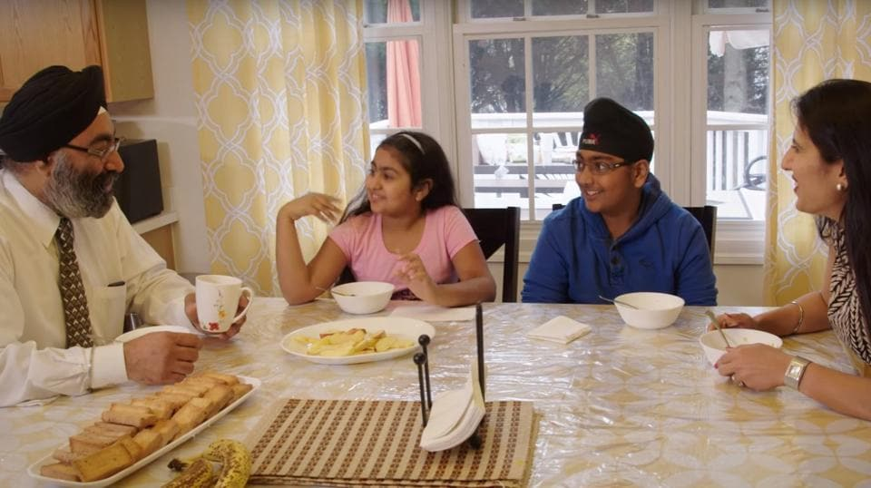 A still from an ad showing a Sikh American family dining together.