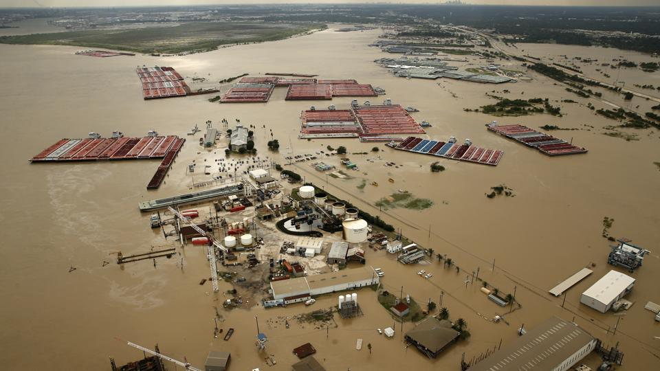 In this Aug. 30, 2017, photo, barges are secured by tugboats in the flood-swollen Burnet Bay along the Houston Ship Channel in Houston.