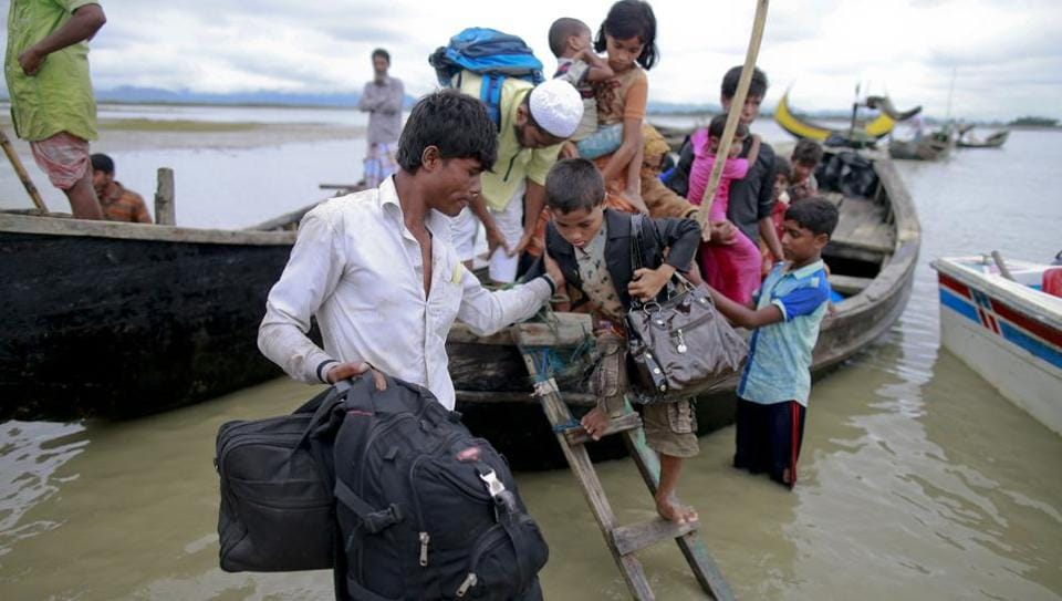 Members of Myanmar's Muslim Rohingya minority get down from a boat after crossing a canal at Shah Porir Deep, in Teknak, Bangladesh, Thursday, Aug. 31, 2017.