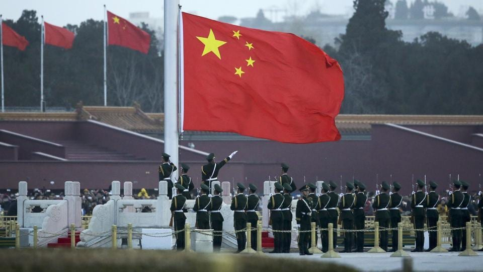 In this March 5, 2016 photo Chinese paramilitary policemen perform a flag raising ceremony on Tiananmen Square in Beijing.