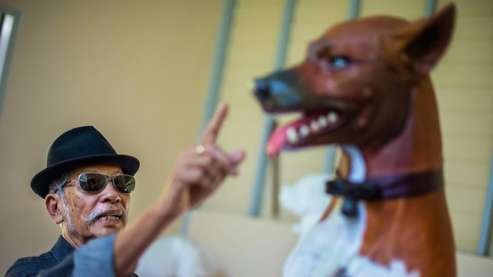 Thai sculptor Chin Prasong gives indications to Pitchapong Parsing (unseen) as Parsing gave the finishing touches of paint to a sculpture of one of the dogs owned by the late Thai King on August 31, 2017.