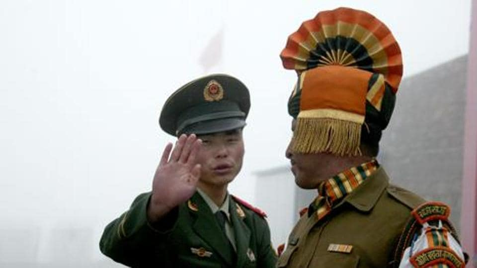 A file photo from  2008 shows a Chinese soldier (L) gesturing next to an Indian soldier at the Nathu La border crossing between India and China in Sikkim. India said August 28, 2017 that troops were disengaging from a months-long stand-off with the Chinese military on a strategically important area of disputed territory in the Himalayas.