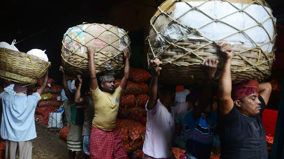 This file photo taken on February 28, 2017 showslabourers carrying baskets of vegetables at the main wholesale vegetable market in Kolkata. India's growth slumped to 5.7 percent in the first quarter of the financial year, official data showed August 31, below predictions as a controversial banknote ban dragged further on the economy.