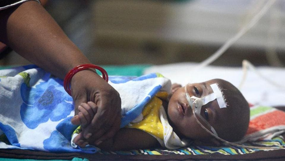A woman holding her child's hand at the encephalitis ward of the Baba Raghav Das Hospital in Gorakhpur on August 14.