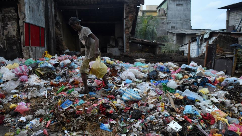 (FILES) This file photo taken on June 26, 2017 shows a Sri Lankan man walking past garbage piled on a street in Colombo. Sri Lanka on September 1 slapped a blanket ban on the import, manufacture or sale of disposable plastic products and polythene shopping bags following environmental concerns.