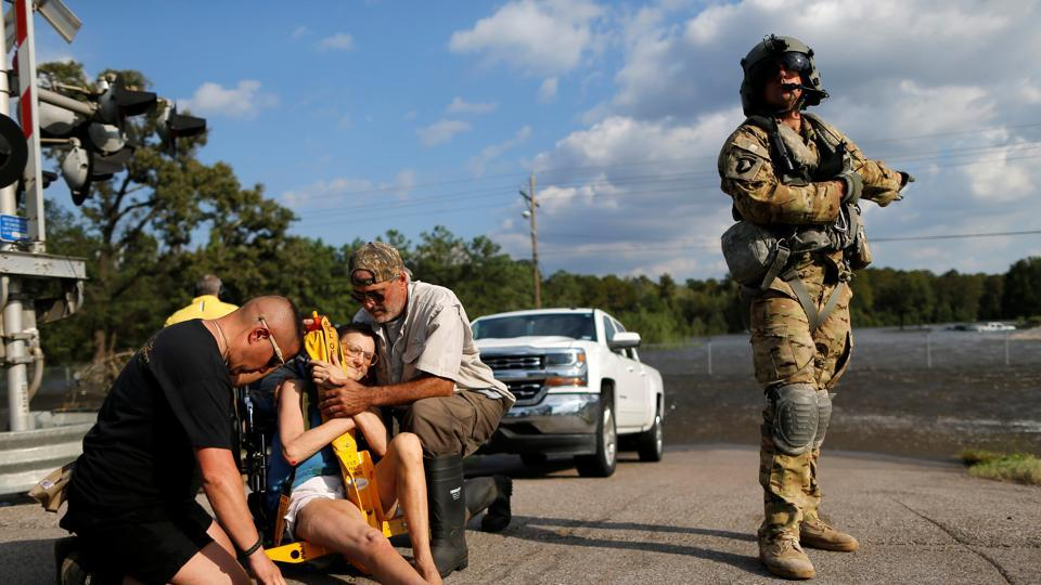 Rescue personnel help Hersey Kirk into a restraint before being airlifted into a rescue helicopter after she was rescued from her home flooded by Tropical Storm Harvey in Rose City, Texas, U.S. on August 31, 2017.