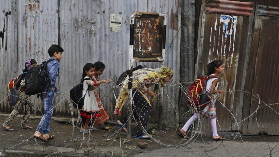 Children cross a temporary check point during curfew in Srinagar.