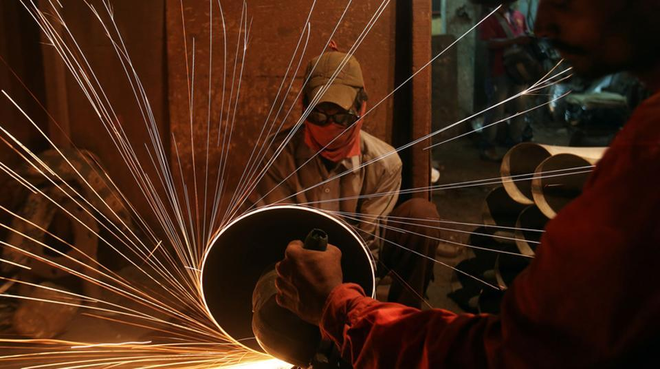 A worker at a workshop that manufactures metal pipes in Mumbai. A survey said the Purchasing Managers' Index (PMI) rebounded to 51.2 in August from 47.9 in July.
