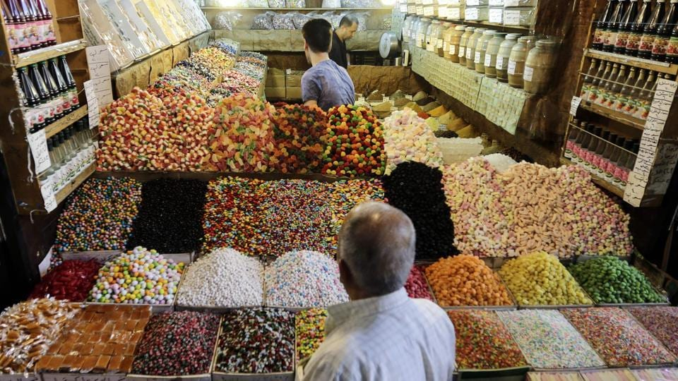 People  buy sweets from a stall at al-Bazourieh popular market in the old part of the capital Damascus, in preparation for celebrations for Eid al-Adha. Syrian President Bashar Assad traveled Friday to a town recently captured from Islamic State group militants to attend Eid al-Adha prayers.  (Louai Beshara / AFP)