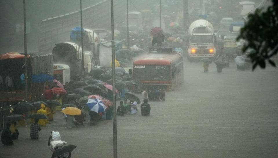 People wade along a flooded street during heavy rain showers in Mumbai on August 29, 2017. Heavy rain brought India's financial capital Mumbai to a virtual standstill on August 29, flooding streets, causing transport chaos and prompting warnings to stay indoors. Dozens of flights and local train services were cancelled as rains lashed the coastal city of nearly 20 million people.