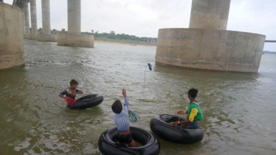 Boys enter river waters on truck tubes, connected with magnets in long ropes.