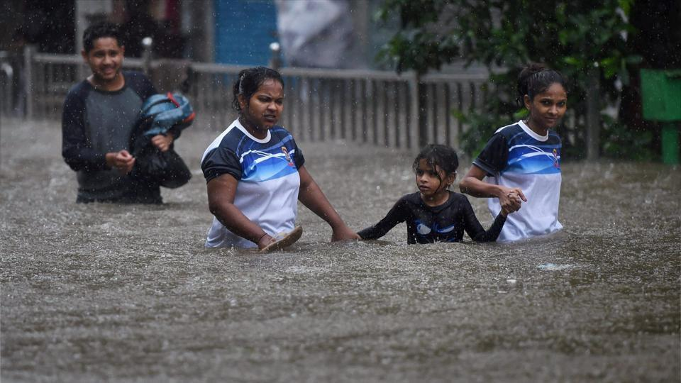 People walk through a flooded street during heavy rains in Mumbai.
