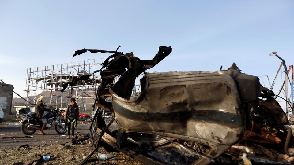 A boy looks at the wreckage of a taxi car destroyed by a Saudi-led air strike on a checkpoint of the armed Houthi movement near Sanaa, Yemen on August 30.