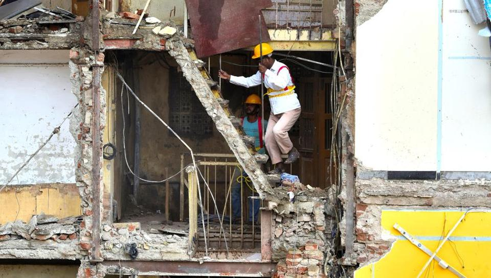 Rescue workers inspect the site of the collapse on Thursday.